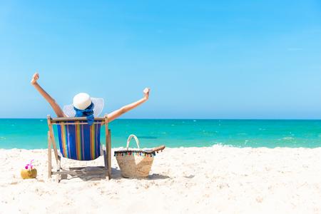 Vacaciones de verano. Mujer asiática joven hermosa que se relaja y feliz en silla de playa con el jugo del coctel del coco en verano del día de fiesta, fondo del cielo azul. Concepto de viaje y estilo de vida