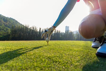 Lady golfer places a golf ball and tee in the ground evening time.   Lifestyle Concept.