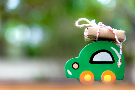 Christmas gift on wood toy car on the road, green backgroud.  Christmas holiday celebration concept Stock Photo