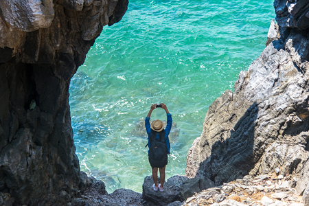 Travel people women tourist take a photo in a cave near the sea in Keo Sichang, Thailand. Travel Concept