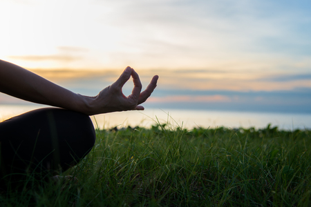 Close up silhouette hands. Woman do yoga outdoor. Woman exercising vital and meditation for fitness lifestyle club at the sunset beach background. Healthy Concept Stock Photo