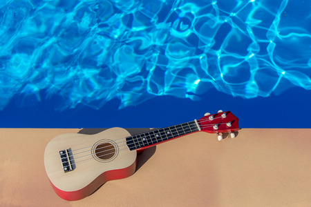 Summer Traveling ukulele near swimming pool at the texture blue water background. Stock Photo