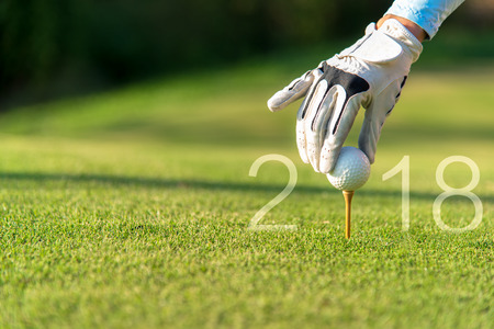 Golfer asian woman putting golf ball for Happy New Year 2018 on the green golf, copy space.   Healthy and Holiday Concept.