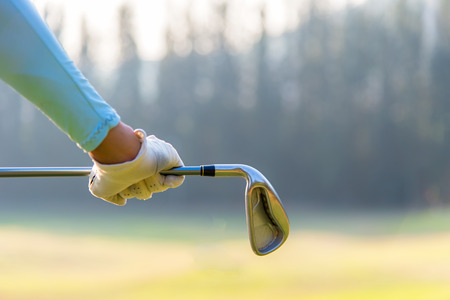 Golf player woman holding a golf club in golf course.  Lifestyle Concept