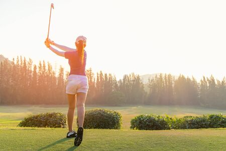 Asian woman golf player doing golf swing tee off on the green sunset evening time, she presumably does exercise.  Healthy and Lifestyle Concept. Foto de archivo