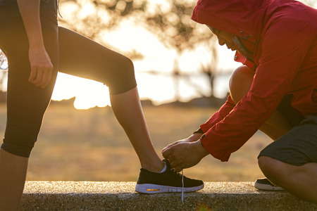 Runners couple tying running shoes to run banner. Trainer lacing woman's shoes laces for jogging motivation at park. Healthy lifestyle  Concept. Stock Photo