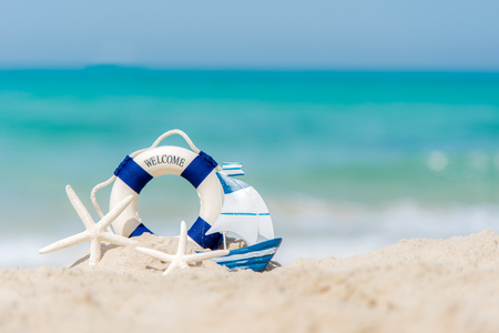 Lifebuoy on sand beach background with starfish and fishing boat, copy space.  Summer Concept Stock Photo