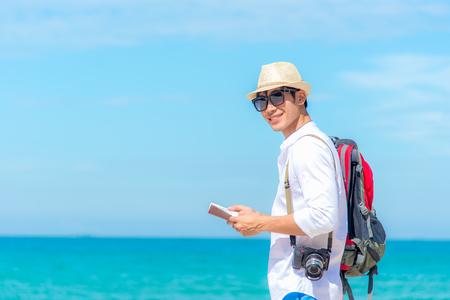 ビーチでカメラでパスポートを探している幸せな笑顔の白人観光客アジアの若者。 夏と旅行のコンセプト。