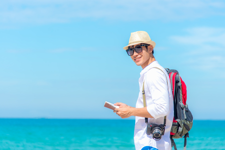 Happy smiling caucasian tourist asian young man looking passport with camera on the beach.  Summer and Travel Concept.