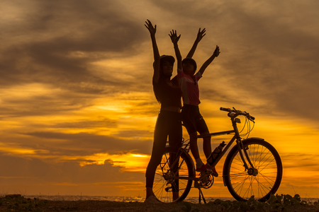 Silhouette biker lovely family at sunset over the ocean.  Mom and daughter bicycling at the beach.  Lifestyle Concept.