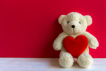 Cute teddy bear with red heart on old wood, copy space, red background. Valentine Concept