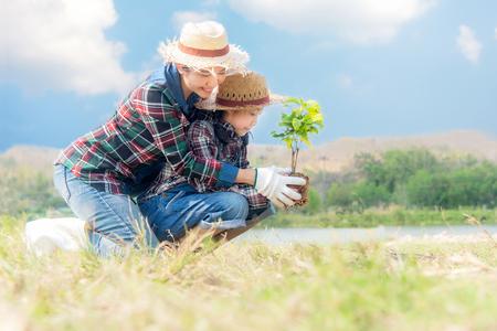 Aziatische moeder en kind meisje plant boompje boom in de natuur lente voor het verminderen van de opwarming van de aarde groeifunctie, vermindering van de opwarming van de aarde en zorg voor de natuur aarde, blauwe hemel achtergrond. Stockfoto