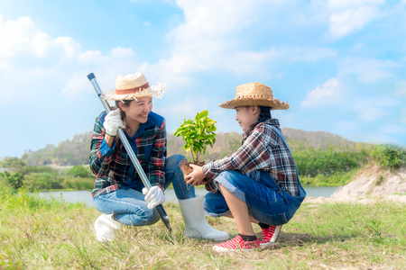 Asian Mom and child girl plant sapling tree in the nature spring for reduce global warming growth feature, reduce global warming and take care nature earth,  blue sky background.
