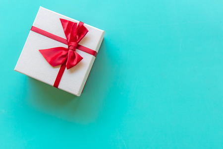 Valentine's day white gift box with a red bow on color full wall background, copy space. Valentine Concept.