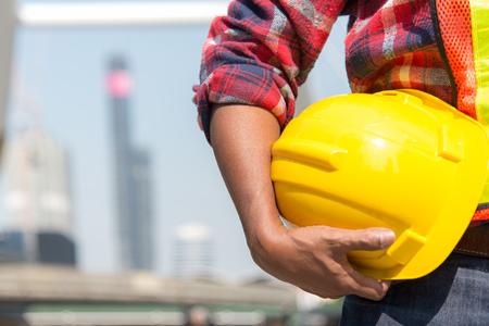 Trabajador del arquitecto que sostiene el casco amarillo a para el control de seguridad de los trabajadores en el sitio de la ciudad.