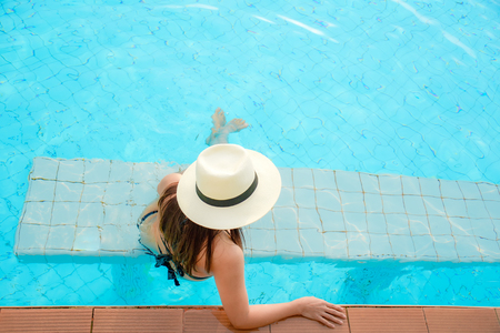 Summer Vacations.  Lifestyle woman happy with bikini and big hat relaxing on the swimming pool, travel near the sea and beach in holiday. Summer Concept Stock Photo