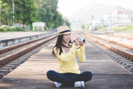Traveler and tourist asian women wearing backpack holding camera and sit near station the train. Travel Concept.