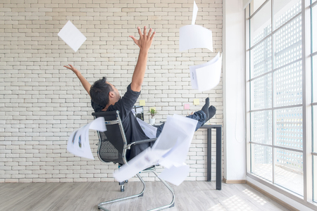 Asian businessman tossing a bunch of papers celebrating the end of his work and success report. He relax and happy with your work.  Business Concept