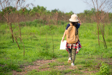 Children asian girl walking and holding maps and travel backpacks in the forest for education nature. Travel Concept Stock Photo
