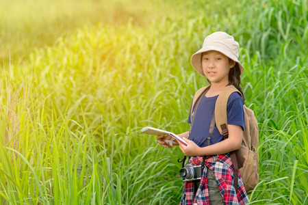 Children asian girl holding maps and travel backpacks walking in the green forest.  Travel Concept Stock Photo