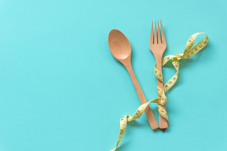 Yellow Measuring tape wrapped around wood fork lying on aquamarine background. Diet and Healthy Concept. Stock Photo