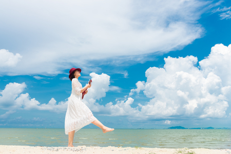 Summer Vacation. Smelling asian women relaxing and playing an ukulele on the beach, so happy and luxury in holiday summer, blue sky background.