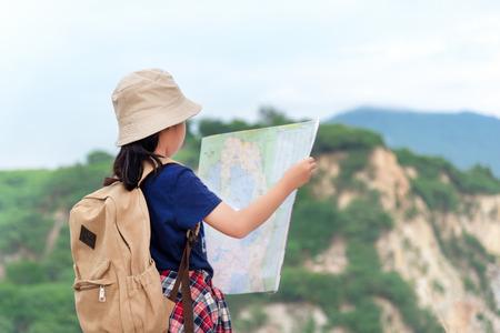 Bambini ragazza asiatica con mappe e zaini da viaggio bussola magnetica in piedi in montagna per l'istruzione natura. Concetto di viaggio