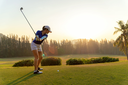 Asian woman golf player doing golf swing tee off on the green sunset evening time, she presumably does exercise. Healthy and Lifestyle Concept. 写真素材