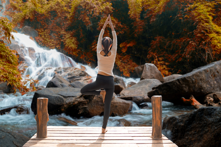 Healthy woman lifestyle balanced practicing meditate and zen energy yoga on the bridge in morning the autumn waterfall in nature. Healthy life Concept. Imagens