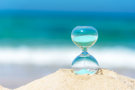 Hourglass summer and vacations time on a beach in the sand  with blue sky and copy space.  Lifestyle Concept. Stock Photo