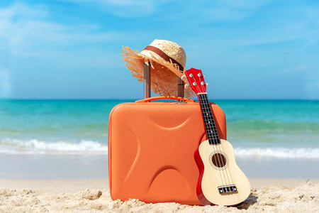 Vacation holiday traveling and planning with old suitcase guitar and hat on the sand beach. Travel in the holiday.   Summer and Travel Concept