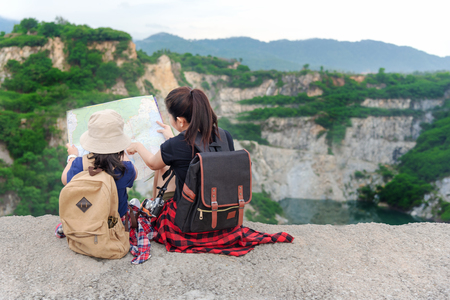 Mom and kid holding maps and travel backpacks sitting victorious facing on the outdoors grand canyon for education nature. Travel Concept