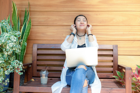 Lifestyle women freelance enjoy listening music and play laptop outdoors work space in the coffee shop for working . Music and Lifestyle Concept. Stock Photo