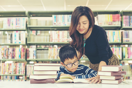 Asian boy reading books for education and go to school with the guidance of him mother in library .  Education and Lifestyle Concept