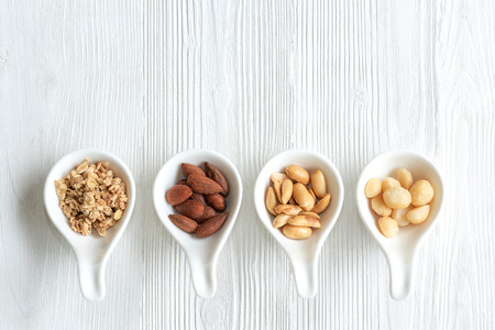 Healthy Foods. Mixed nuts in white bowls with nuts for diet on white table. Different kinds of tasty and healthy nuts. Top view and copy space.  Healthy Concept Banco de Imagens - 120819670