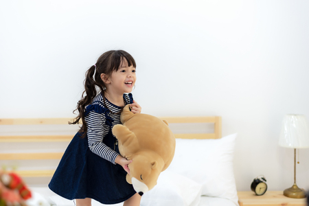 Funny happy toddler girl jumping and playing with her toy teddy bear in bed. Kids play at home. White nursery. Child in sunny bedroom Banco de Imagens - 120819675