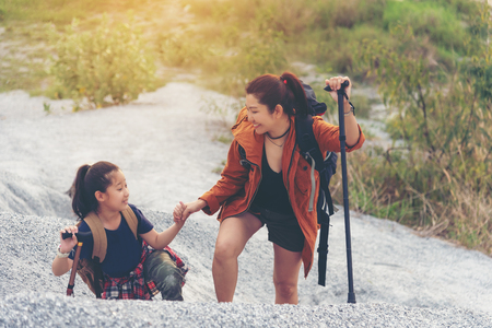 Mom and kid travel backpacks standing in the mountain for education nature. Travel Concept Banco de Imagens