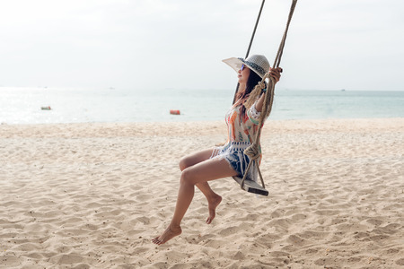 Summer Vacations. Lifestyle women relaxing and enjoying swing on the sand beach, fashion stunning women with white dress on the tropical island so happy and luxury in holiday summer. Travel and Summer Concept