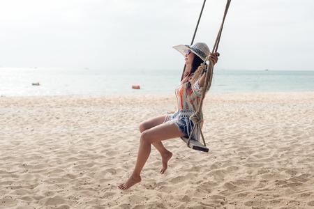 Vacaciones de verano. Mujeres de estilo de vida relajándose y disfrutando del swing en la playa de arena, moda a mujeres deslumbrantes con vestido blanco en la isla tropical tan felices y lujosas en vacaciones de verano. Viajes y concepto de verano