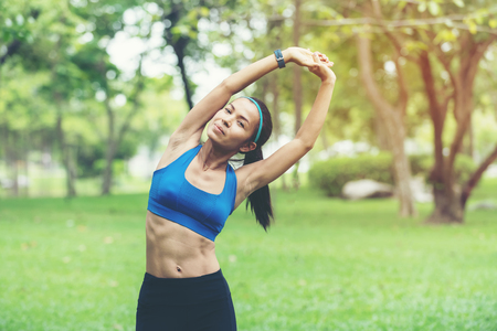 Healthy smiling woman warming up stretching her arms and looking away in the outdoor.  Asian runner woman workout before fitness and jogging session at the park.   Healthy and Lifestyle Concept. Banco de Imagens - 120819378