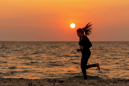 Silhouette runner feet running on the beach in the sunset outdoor. Asian fitness and sporty woman running for healthy and relax.  Sport Concept Banco de Imagens - 120819657