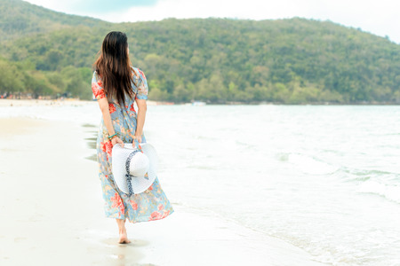 Summer Holiday. Lifestyle woman chill holding big white hat and wearing fashion summer trips walking on the sandy ocean beach. Happy woman enjoy and relax vacation. Lifestyle and Travel Concept