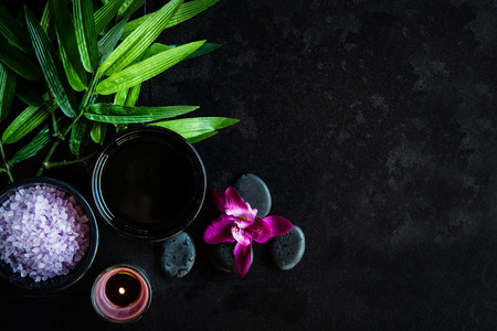 Thai Spa.  Top view of hot stones setting for massage treatment and relax with purple orchid on blackboard with copy space.  Green leaf with black stones pile for spa therapy.  Lifestyle and Healthy Concept. Banco de Imagens