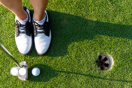 Top View golfer asian sporty woman focus putting golf ball on the green golf.  Healthy and Lifestyle Concept Banco de Imagens