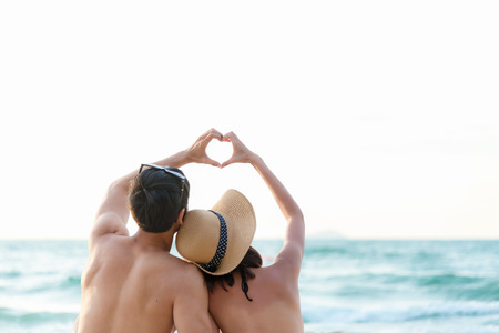 Couple in love making a heart - shape with hands on tropical on the sunset beach in holiday.  Honeymoon relax together on summer travel destination.  Valentine, Travel and Summer Concept