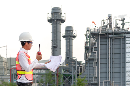 Engineer man holding blueprint with radio for workers security control at power plant energy and petrochemical industry. Engineer Concept Stock Photo