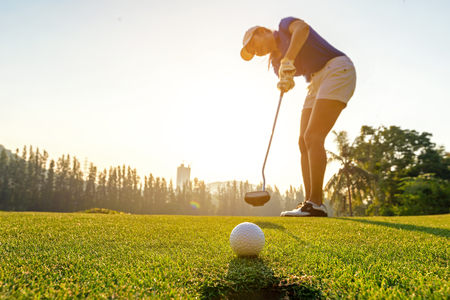 Deporte saludable. Golfista mujer deportiva asiática se centra en poner una pelota de golf en el campo de golf verde en la puesta de sol por la noche. Concepto de estilo de vida y saludable