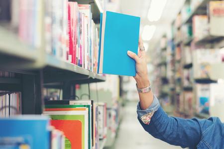 Ciérrese encima de las mujeres del estudiante de la mano que encuentran el libro para leer en la biblioteca. Concepto de educación