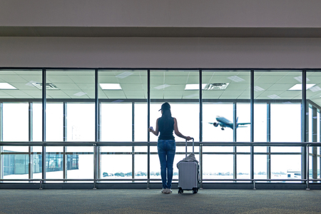 Traveler women plan and backpack see the airplane at the airport glass window, Asian tourist hold bag and waiting near luggage in hall airplane departure. Travel Vacation Concept. Banco de Imagens