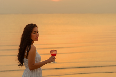 Beautiful lifestyle asian woman enjoy and relax with holding cocktail at sunset beach in holiday summer vacation.  Lifestyle Concept Banco de Imagens - 122127141